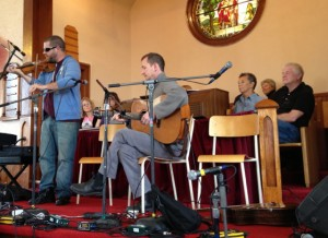 Fiddler and guitarist playing in church.